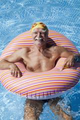 Österreich, erwachsener Mann mit schwimmenden Reifen in Schwimmbad