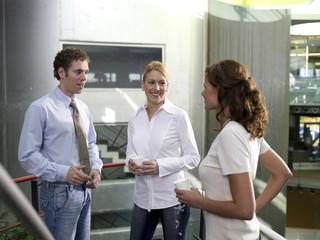 Junge Frau hört Kollegen reden