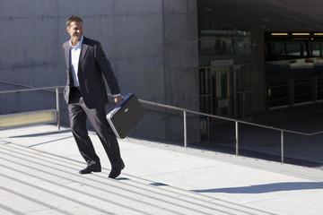 Deutschland, Bayern, München, Geschäftsmann zu Fuß auf der Treppe mit Aktenkoffer