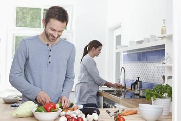 Deutschland, Bayern, München, Mann Hacken Zucchini in der Küche, Frau im Hintergrund