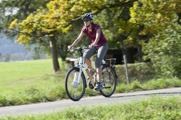Deutschland, Bayern, Frau auf Elektro-Fahrrad