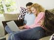 Junges Paar auf dem Sofa mit Laptop