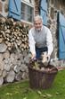 Deutschland, Kratzeburg, erwachsener Mann mit Feuerholz in Korb