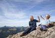 Deutschland, Bayern, Vater und Sohn sitzen auf Berg-Gipfel