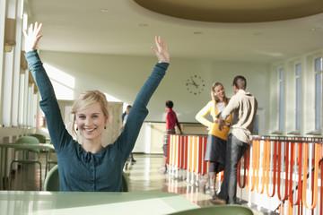Deutschland, Leipzig, Frau hebt die Hände in die Luft, im Hintergrund stehen Studenten