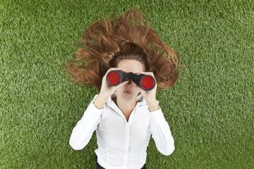 Junge Frau schaut durch ein Fernglas, während Mann im Gras liegt