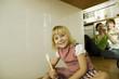 Mädchen in Küche, Eltern im Hintergrund