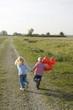 Kleine Jungen und Mädchen mit Luftballons rennen über Feldweg, Rückansicht
