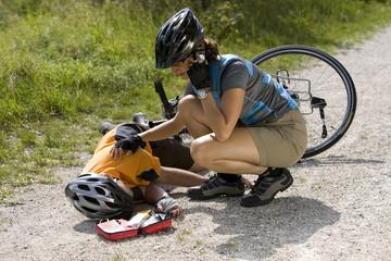 Deutschland, Bayern, Oberland, Frau hilft verunfalltem Biker