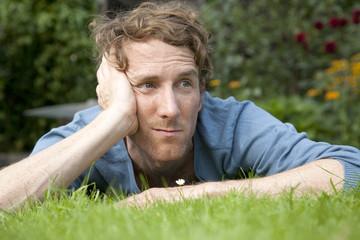 Mann liegt im Gras und denkt nach