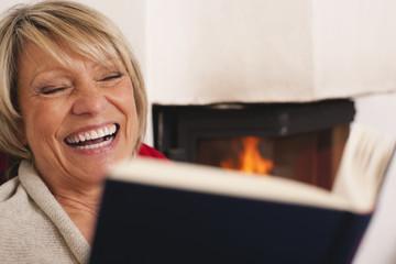 Deutschland, Kratzeburg, ältere Frau, Seniorin liest Buch und lächelt