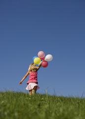 Österreich, Mondsee, Mädchen mit Luftballons auf einer Wiese