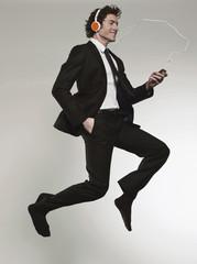Geschäftsmann, Musik hören und springend, Lächeln