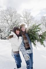 Österreich, Land Salzburg, Flachau, Junger Mann und Frau mit Weihnachtsbaum im Schnee