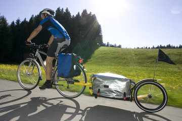 Deutschland, Bayern, Mann fährt Mountainbike mit Anhänger