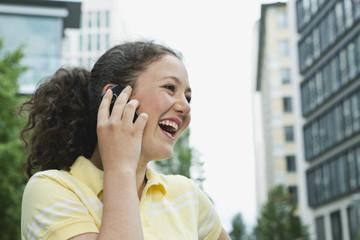 Deutschland, Berlin, Teenager-Mädchen mit Handy in der Stadt, lachen