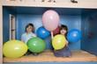 Junge und Mädchen spielen mit Luftballons, Lächeln