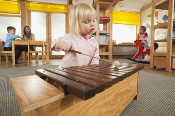 Deutschland, Mädchen spielen Xylophon, Kindergärtnerin mit Kindern im Hintergrund