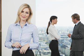 Deutschland, Frankfurt, Geschäftsfrau mit Geschäftsleute reden im Hintergrund