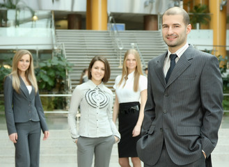 Successful business man standing with his staff