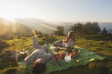 Junges Paar liegt auf einer Decke, mit Frühstück.