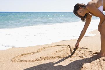 Frankreich, Korsika, Frau Zeichnung Herzform in den Sand am Strand