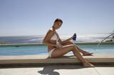 Frau benutzt Sonnencreme im Schwimmbad