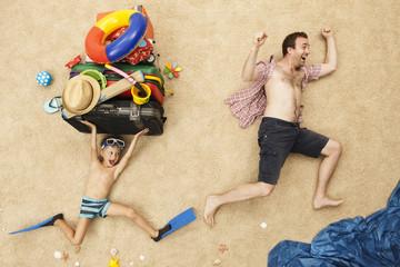 Deutschland, Vater und Sohn mit Spielzeug und Gepäck am Strand