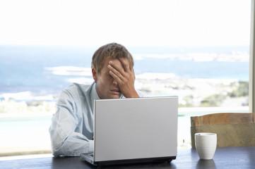 Mann sitzt am Tisch, mit Laptop