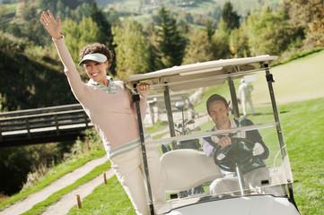 Italien, Kastelruth, Golfer in Golfwagen auf Golfplatz