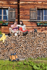 Österreich, Salzburg, Paar sitzt auf Holz vor Hütte