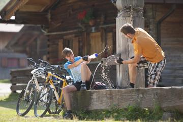 Österreich, Tirol, Mann und Frau spielen mit Wasser Wasserpumpe