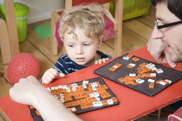 Deutschland, Berlin, Vater und Sohn spielen mit Buchstaben