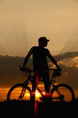 Deutschland, Niederbayern, Biker mit Fahrrad bei Sonnenuntergang