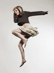 Frau springt vor grauem Hintergrund