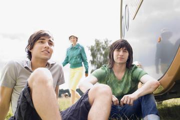 Deutschland, Leipzig, Ammelshainer See, junge Männer sitzen in der Nähe ihres Wohnwagens