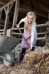 Deutschland, Sachsen, Junge Frau arbeitet in der Farm