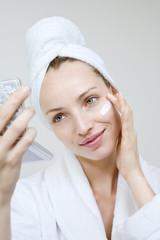 Junge Frau benutzt Schönheitscreme