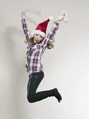 Mädchen mit Weihnachtsmütze springt und hält Schal