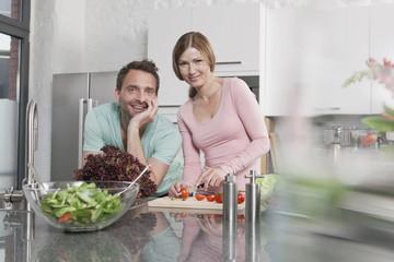 Deutschland, Paar bereitet Salat in der Küche, Lächeln