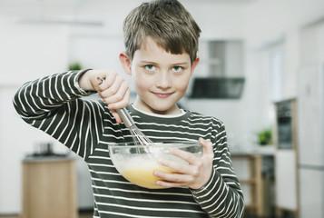 Deutschland, Köln, Junge isst Teig aus Schüssel