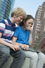 Deutschland, Berlin, Teenage Paar mit Laptop in der Stadt