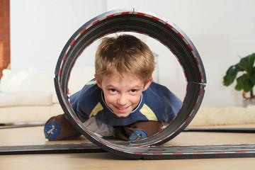 Kind gerade durch Spielzeug Rennstrecke