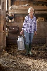 Deutschland, Sachsen, Seniorin mit Milchkanne in der Farm