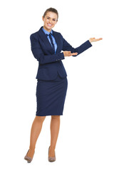 Full length portrait of happy business woman showing something