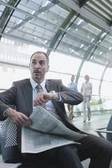 Deutschland, Leipzig-Halle, Flughafen, Geschäftsmann mit Zeitung, Geschäftsleute im Hintergrund
