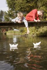 Junge und Mädchen auf der Brücke beobachten Papier Boote im Wasser