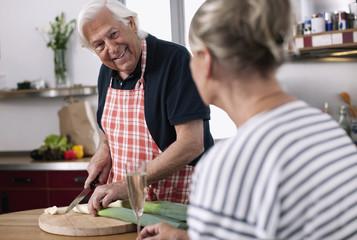 Deutschland, Wakendorf, Senior, Rentner schneiden Gemüse mit Frau im Vordergrund