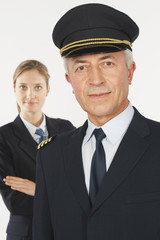 Nahaufnahme von Pilot und junge Stewardess vor weißem Hintergrund