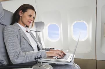 Deutschland, Bayern, München, Mitte Erwachsener Geschäftsfrau mit Laptop in der Business Class Flugzeugkabine